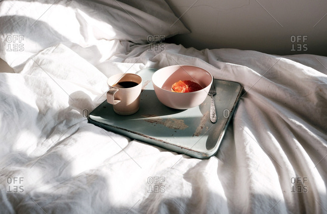 Grapefruit breakfast in bed with morning light and coffee