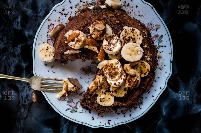 A forkful of cacao pancakes covered in banana, nuts and honey