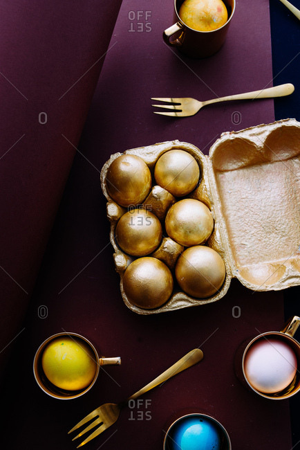 Luxury Easter concept, colored eggs inside golden cup with cutlery