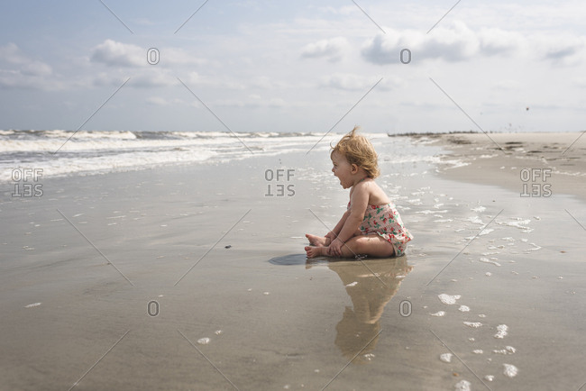 Side view of baby girl screaming while sitting at beach against sky