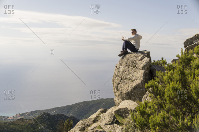 Side view of man looking at view while mountain against sky during sunny day