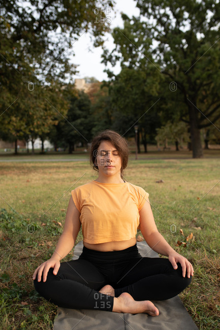 Woman meditating outdoors in a park