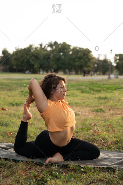 Young woman doing a one-legged king pigeon yoga pose at the city park