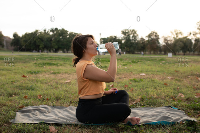 Woman drinking water after an exercise in the park