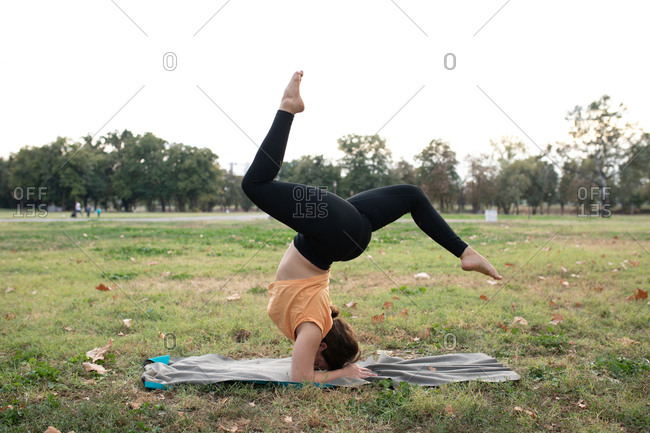 Woman doing acro yoga in the park