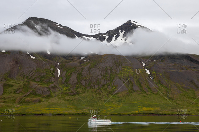 Stykkisholmur, Iceland - July 8, 2019: Boats passing by mountains on the coast of Iceland