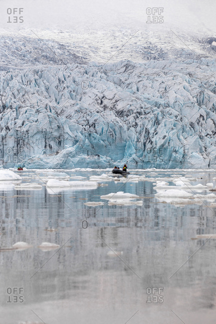 Men traveling by boat in the icy waters off the coast in Iceland