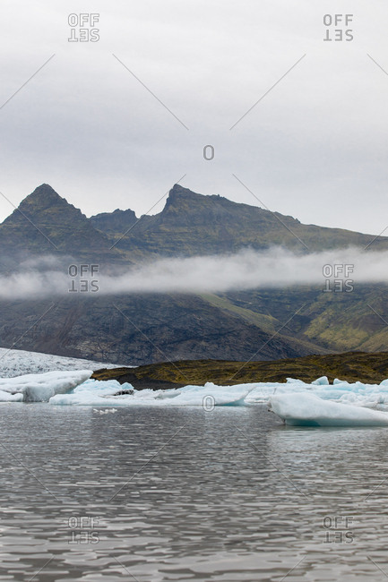 Low lying clouds over mountains on the icy coast of Iceland
