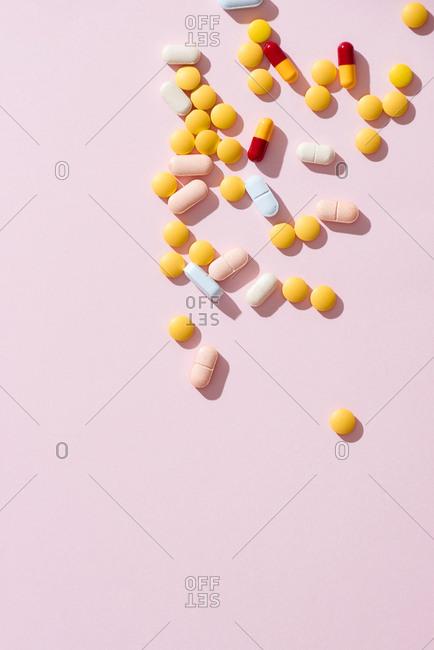 Many kind of medicine on pink background.