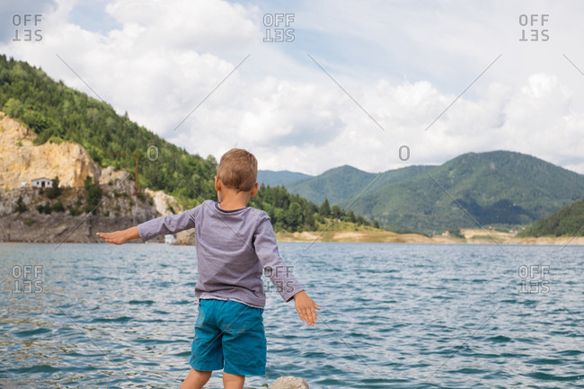 Rear view of a young boy looking out at water and mountains