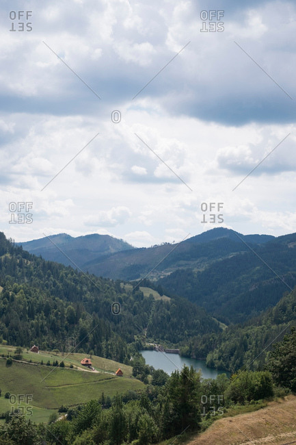 Bird's eye view over lake nestled in rolling green hills under