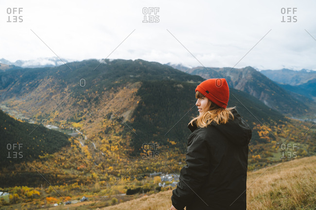Young blonde girl wearing a red beanie admiring the beautiful landscape of Aran Valley
