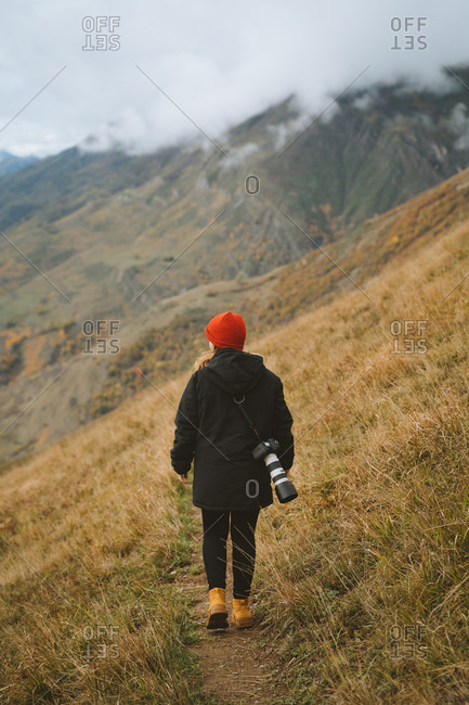 Girl wearing a red beanie taking photos on a cloudy day up in the Pyrenees mountains