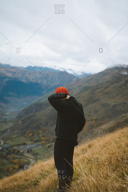 Young boy wearing a red hat carrying a camera on the mountain