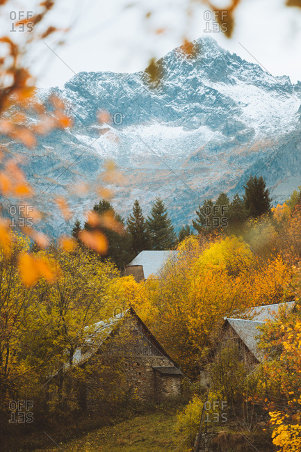 Small cabins in autumn with snowy mountains on the background
