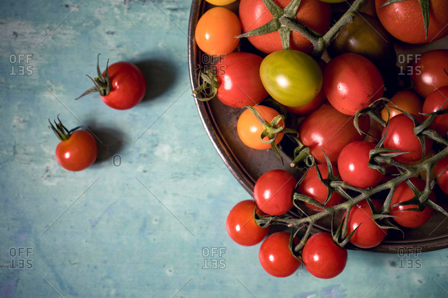 Colorful tomatoes on a pewter plate over old, painted wood background