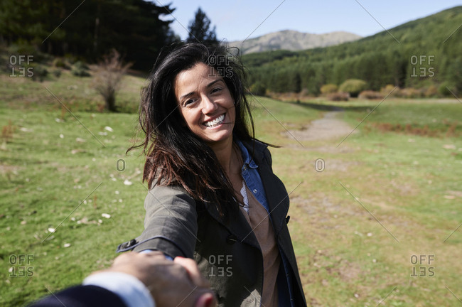 POV of a smiling young woman leading a man by the hand along a path during an outdoor hike together