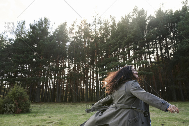 Carefree young woman smiling and spinning around while walking along along a treelined path in the countryside