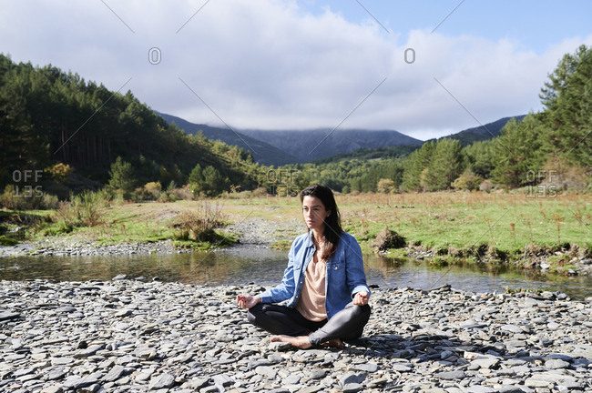 Young woman sitting with her legs crossed by a river and meditating during a yoga session outdoors