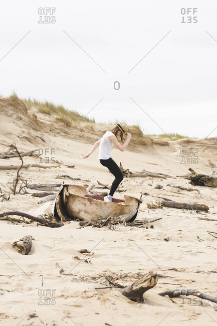 Side view of teenage girl dancing on abandoned boat at beach against sky during sunny day