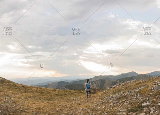 Rear view of female hiker with backpack looking at view while standing on mountain against cloudy sky during sunset