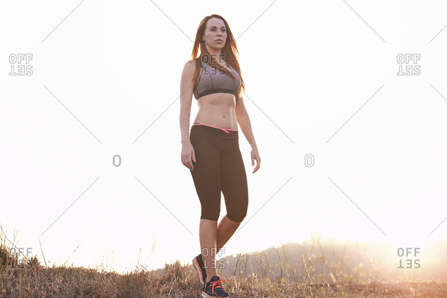 Low angle view of thoughtful woman wearing sports clothing while standing on field against clear sky