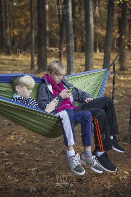 Brothers using smart phones while sitting on hammock in Banff National Park