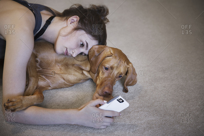 High angle view of woman with dog taking selfie while lying on rug at home