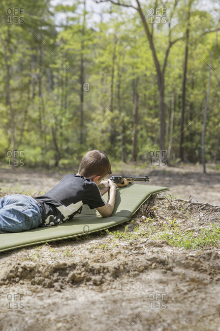 Side view of boy aiming rifle while lying on mat in forest