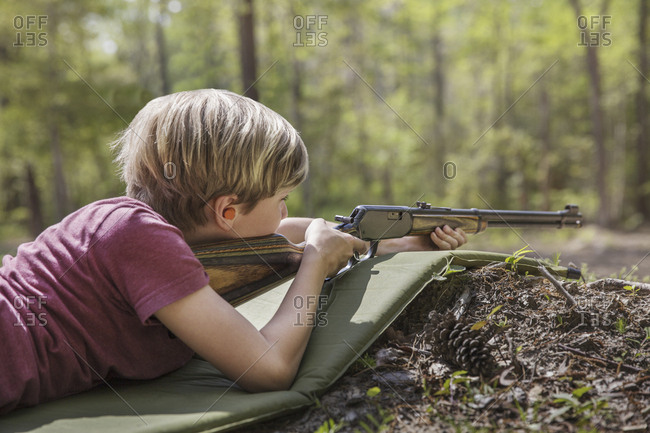 Boy aiming rifle while lying on mat in forest