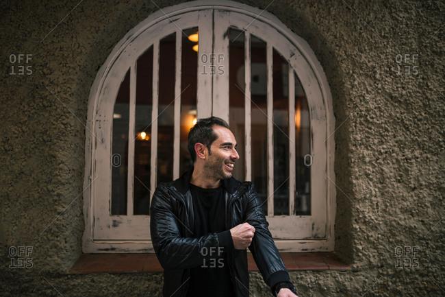 Cheerful man adjusting jacket sleeve while standing against window