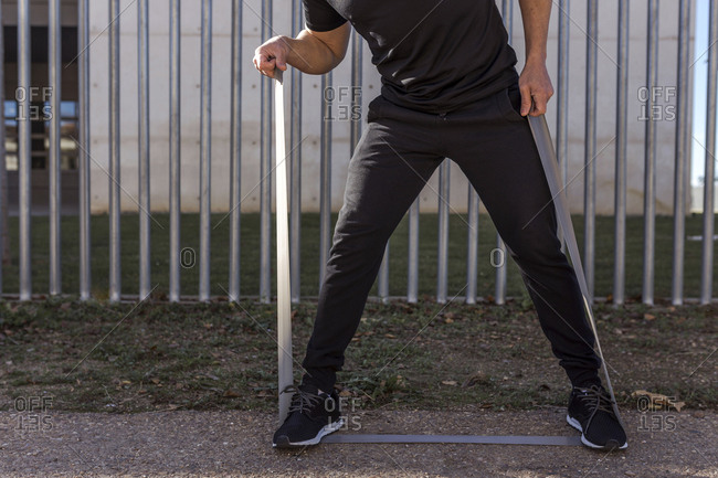 Low section of man exercising with resistance band on field