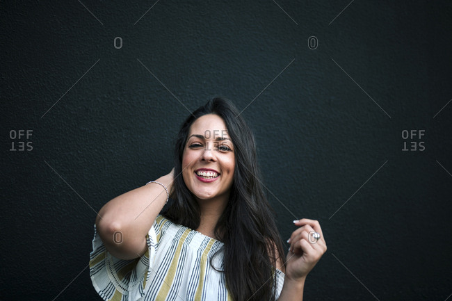 Cheerful woman with hand in hair standing against wall