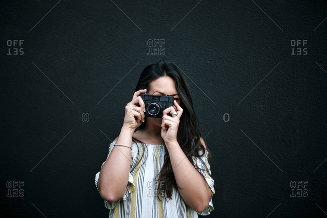 Woman photographing with digital camera while standing against wall