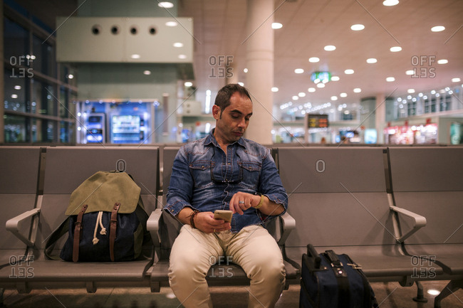 Man checking time while sitting on chair in airport departure area
