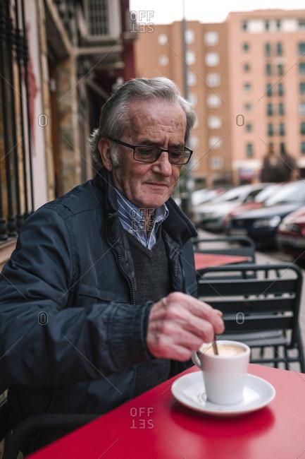 Senior man having coffee while sitting at sidewalk cafe