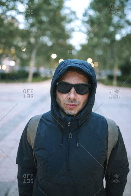 Portrait of man wearing sunglasses and hooded jacket while standing against trees in park