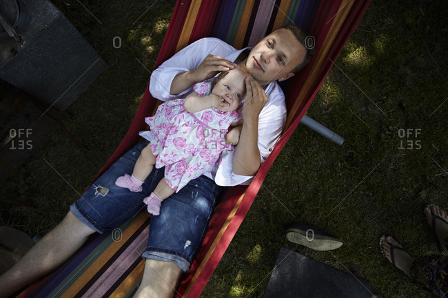 Overhead view of father with daughter relaxing in hammock