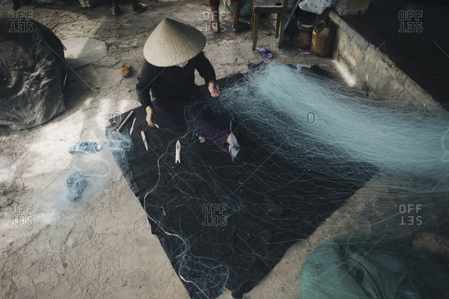 High angle view of person in conical hat repairing fishing net