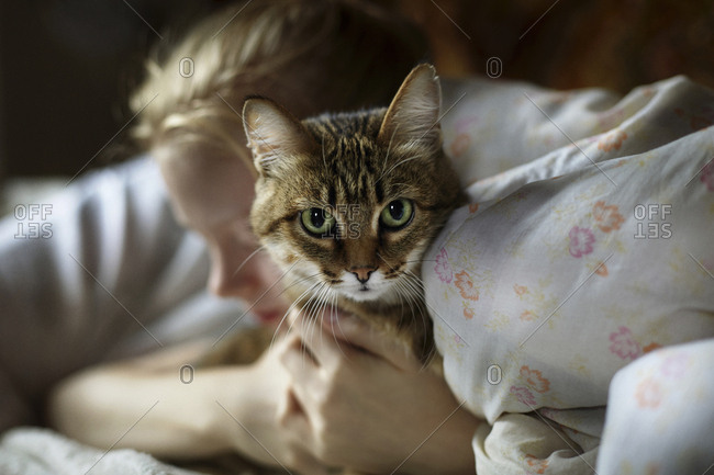 Woman embracing cat while lying on bed at home