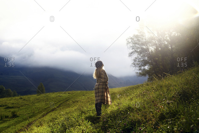 Woman looking away while standing on grassy field against sky