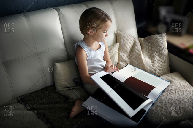 High angle view of girl looking at color swatch book while sitting on sofa