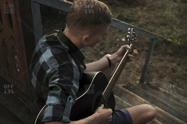 High angle view of man playing guitar while sitting on steps in porch