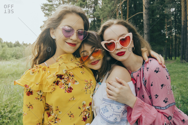 Loving female friends wearing sunglasses embracing in forest