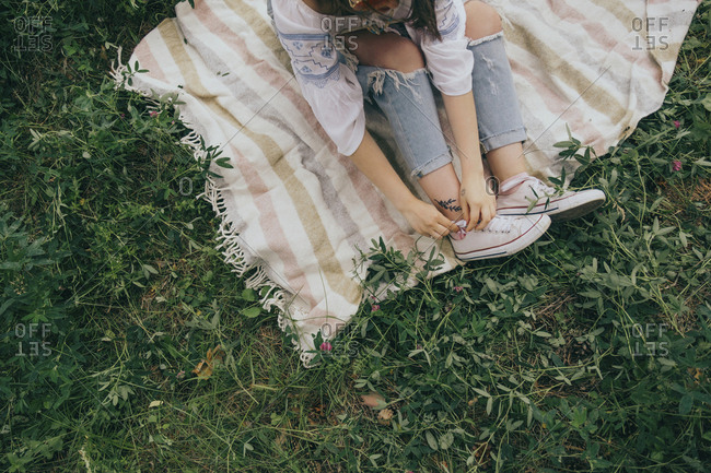 High angle view of young woman typing shoelace while sitting on picnic blanket in forest