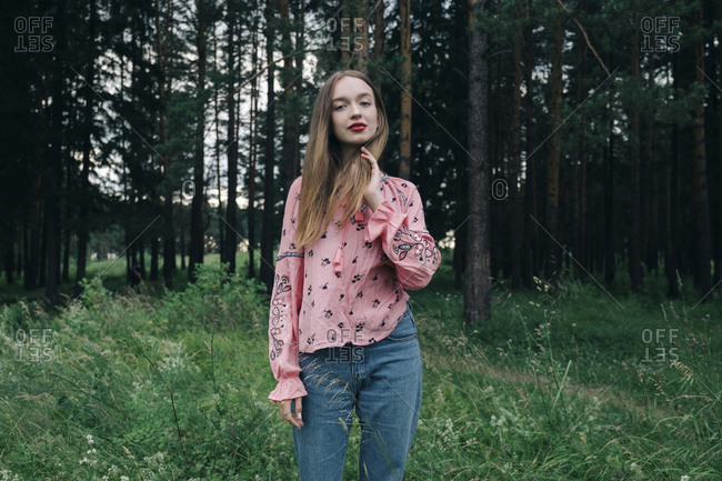 Portrait of confident young woman standing in forest