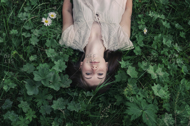 High angle portrait of carefree young woman lying amidst plants on field in forest
