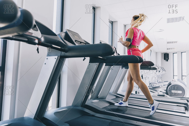 Side view of woman running on treadmill at gym