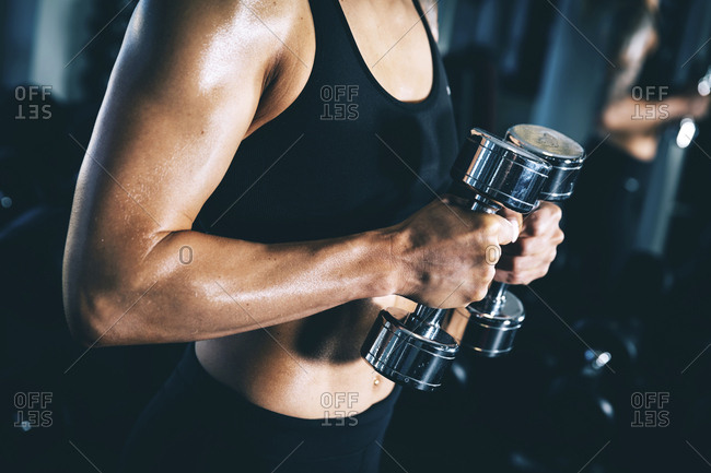 Midsection of woman lifting dumbbells in gym