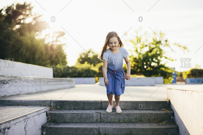 Playful girl jumping on steps against clear sky during sunset